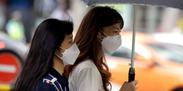 Tourists wear masks as a precaution against MERS (Middle East Respiratory Syndrome) at a shopping district...