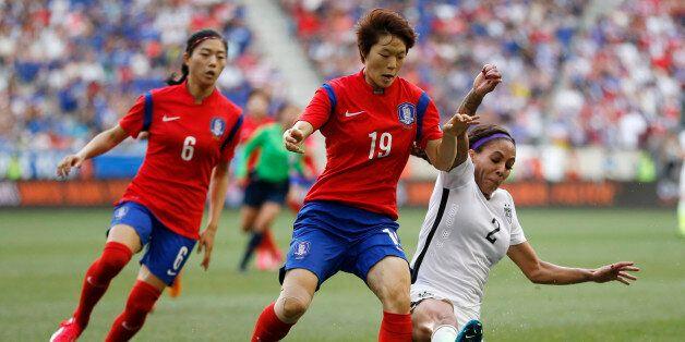 United States forward Sydney Leroux, right, slides for the ball as South Korea defender Kim Doyeon, center,...