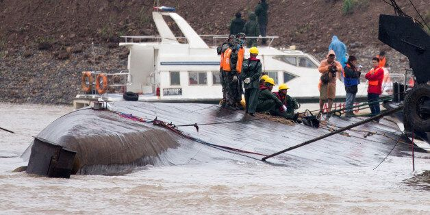 Chinese soldiers stand as rescuers conduct a search and rescue operation on the capsized ship, center,...