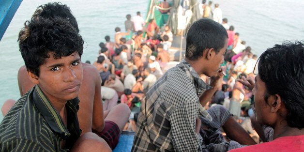 Migrants sit on their boat as they wait to be rescued by Acehnese fishermen on the sea off East Aceh,...