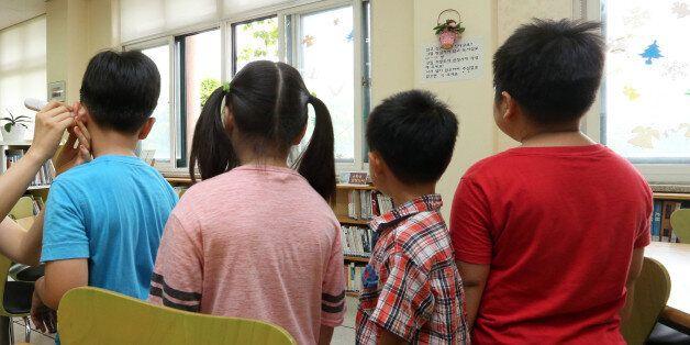 중동호흡기증후군(메르스)로 지역별 학교 휴업이 계속된 11일 서울 용산구 한 초등학교에 등교한 일부 학생들이 교사의 지도를 받으며 발열체크를 하고