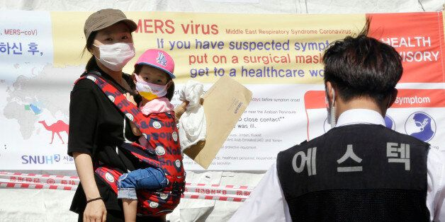 A mother and her daughter wearing masks walk near a precaution against the MERS, Middle East Respiratory...