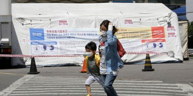 A mother and her son wearing masks pass by a precaution against the MERS, Middle East Respiratory Syndrome,...