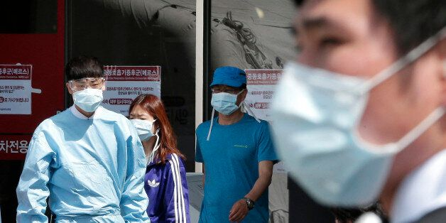 Hospital workers and visitors wearing masks pass by a precaution against the MERS, Middle East Respiratory...
