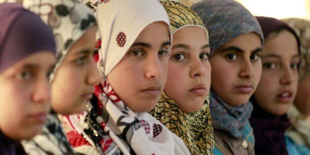 Syrian refugee girls sit at the United Nations Children's Fund (UNICEF) 'Child Friendly Spaces' (CFSs)...