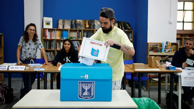 A man casts his vote as he holds up a small placard during Israel's parliamentary election, at a polling station in Tel Aviv, Israel September 17, 2019. REUTERS/Corinna Kern