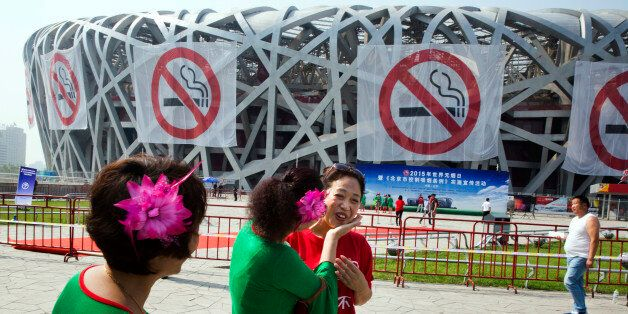 Square dance performers chat near anti-smoking banners displayed on the iconic Bird's Nest National Stadium...