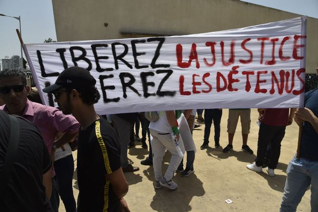 Algerians wave a banner reading in French