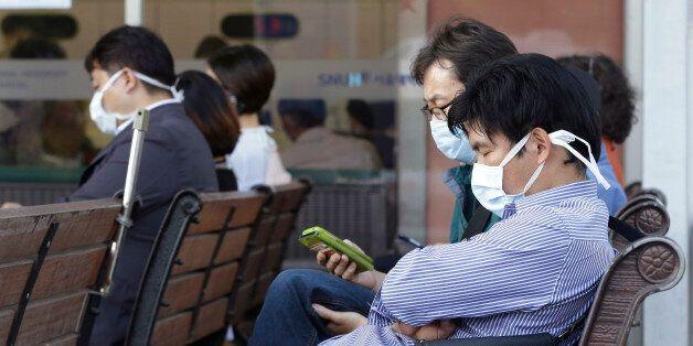 South Koreans wearing masks as a precaution against the Middle East Respiratory Syndrome virus sit at...