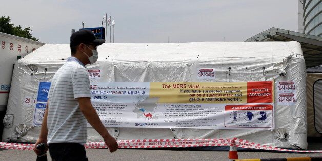 A man wearing mask walks near a precaution against the MERS, Middle East Respiratory Syndrome, virus...