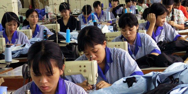 ** FILE ** Vietnamese workers use sewing machines at a state run garment factory to manufacture sporting...