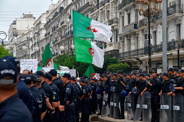 Algerian protesters wave their national flags next to security forces during a demonstration against...