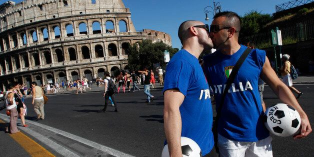 A couple wearing Italy's national soccer team t-shirts kiss during a Gay Pride Parade as the demonstration...