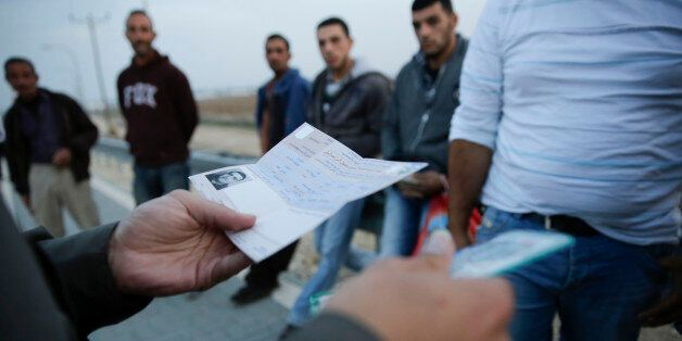 Israeli border policeman checks ID's and work permits of Palestinian workers, as they head back home...