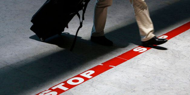 A passenger crosses a stop line as he arrives at Roissy Charles de Gaulle airport in Roissy, north of...