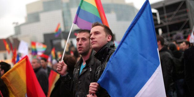 People holding the French and the rainbow flags attend the