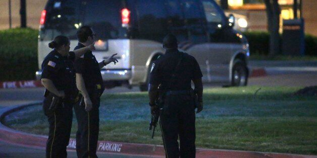 Police officers stands guard at a parking lot near the Curtis Culwell Center where a provocative contest...