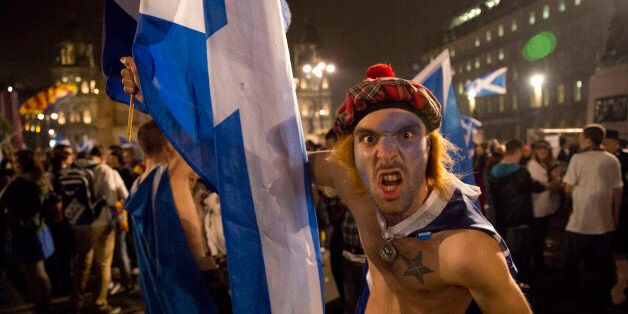 A supporter of the Yes campaign in the Scottish independence referendum pulls a face in good humor as...