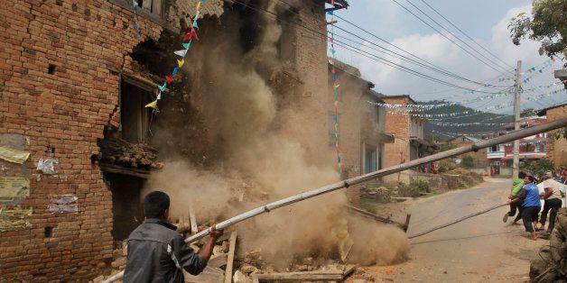 The walls of a damaged home crumble as it is knocked down by people in Lalitpur, Nepal, Friday, May 8,...