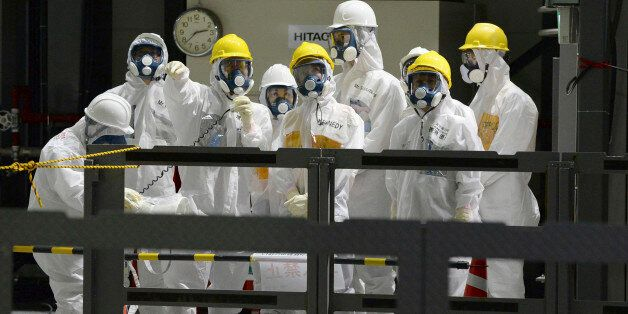 U.S. Ambassador to Japan Caroline Kennedy, front row center, wearing a yellow helmet, a protective suit...