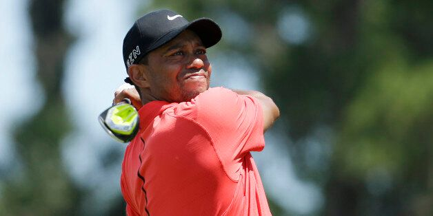 Tiger Woods hits from the 16 tee during the final round of The Players Championship golf tournament Sunday,...