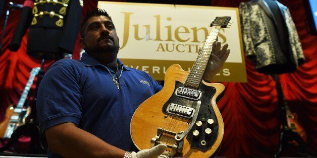 An employee of Julien's Auctions shows musician George Harrison's Mastersound Electric Guitar before...