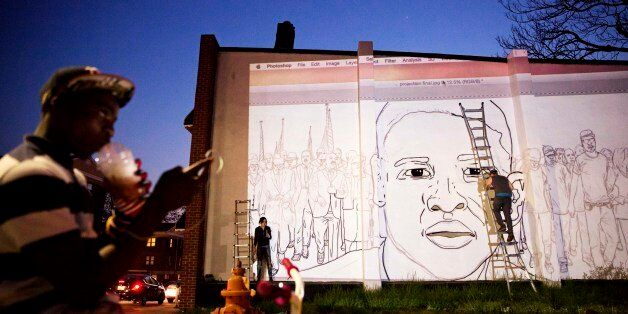 A mural of Freddie Gray is painted on the side of a building by local artist Nether, right, across the...