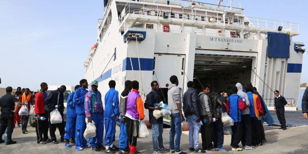 Migrants board on a ferry as they leave the Island of Lampedusa, Southern Italy, to be transferred in...