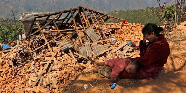 A Nepalese woman sits with her son near their house, destroyed in last week's earthquake, in Pauwathok...