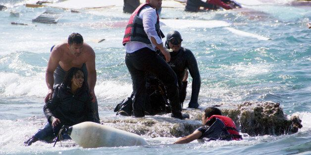 A man rescues an migrant from the Aegean sea, in the eastern island of Rhodes, Monday, April 20, 2015....