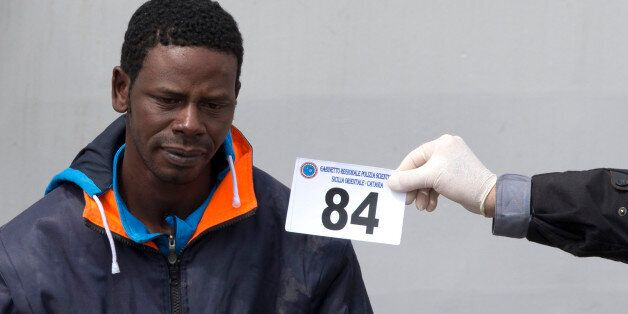 An Italian forensic police officer holds a numbered tag as he identifies a man who disembarked from the...