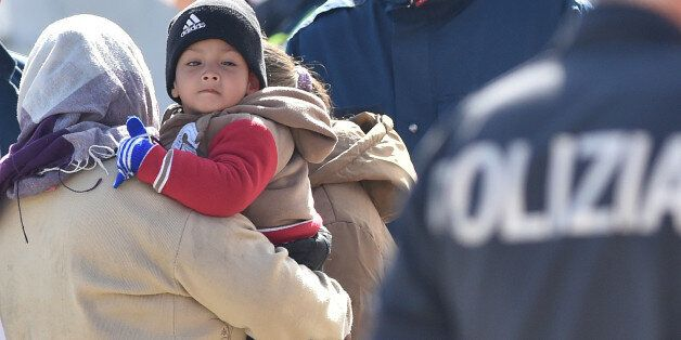 Migrants receive first aid upon disembarking from Italian Navy