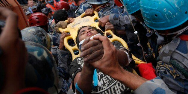 A Nepalese man being rushed to hospital on a stretcher after being rescued by Nepalese policemen and...