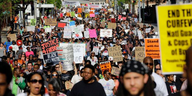 Protesters march through Baltimore on Saturday, May 2, 2015, the day after charges were announced against...