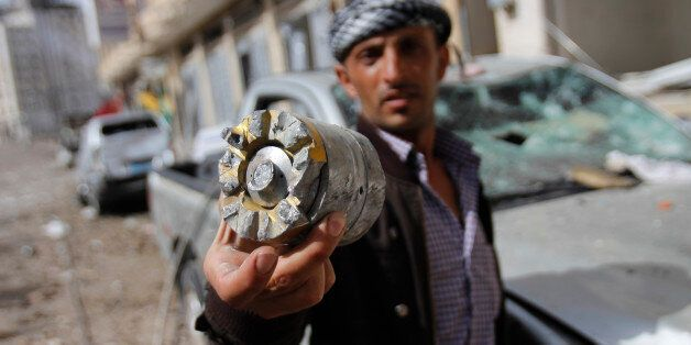 A man holds a projectile fragment after a Saudi-led airstrike against Iran-allied Shiite rebels, known...