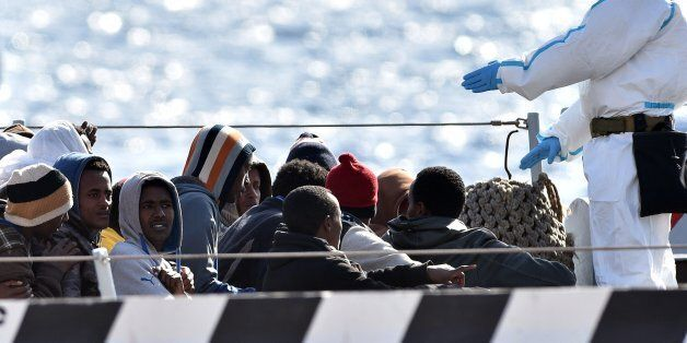 An Italian Navy officer gives instruction to migrants who are waiting to disembark from Italian Navy