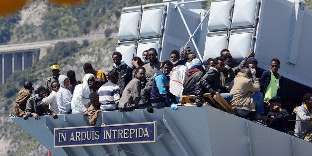 Migrants wait to disembark from the Italian Navy vessel 'Chimera' as a plaque reads in
