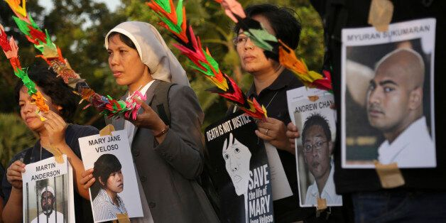 Indonesian activists hold portraits of inmates, all convicted on drug charges, during a demonstration...