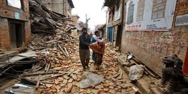 An elderly injured woman is taken home through earthquake debris after treatment in Bhaktapur near Kathmandu,...