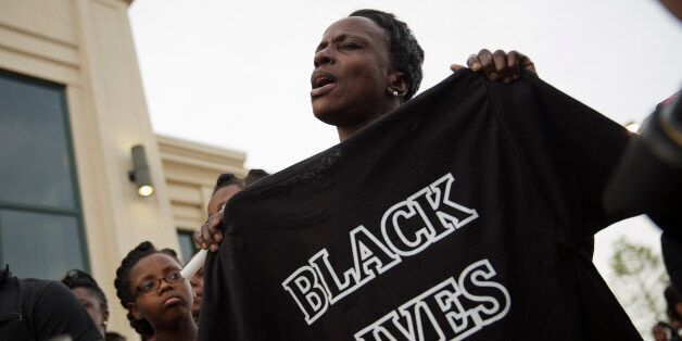 A woman sings while holding a t-shirt during a rally protesting the shooting death of Walter Scott, Friday,...