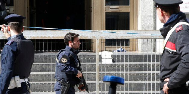 A policeman runs out of the tribunal building in Milan, Italy, after a shooting was reported inside a...
