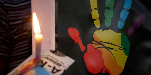 A lit candle is held by a protester in front of a placard during a rally to demand justice in the killing...