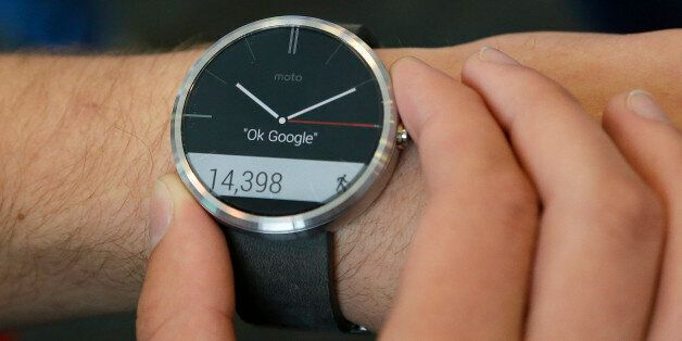 A man wears a Moto 360 by Motorola, an Android Wear smartwatch, on the demo floor at Google I/O 2014...