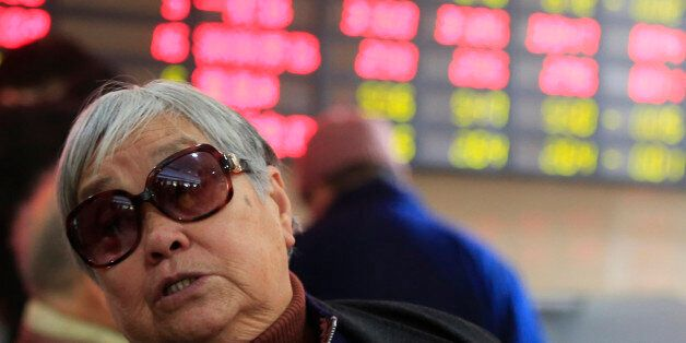 An investor looks at the stock price monitor at a private securities company Thursday, Dec. 19, 2013...