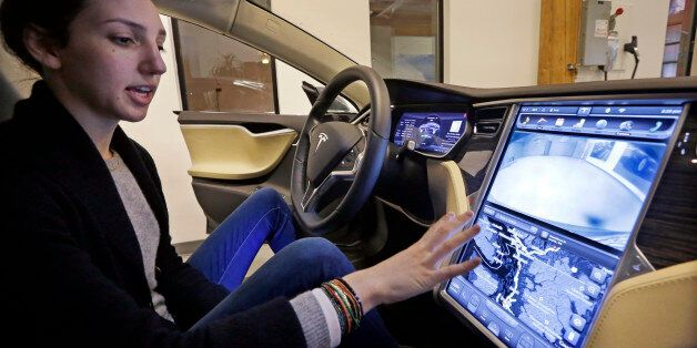 Tesla product specialist Kat Brand explains the control panel on the electric car at a dealership for...