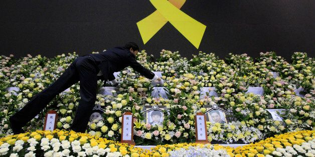 A funeral service employee sets up a group memorial altar for victims of the sunken ferry Sewol in Ansan,...