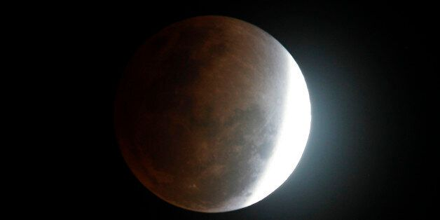 The moon seen from Manila, Philippines, during a total lunar eclipse Saturday Dec. 10, 2011, as the Earth...