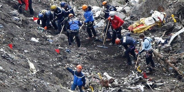 Rescue workers work on debris of the Germanwings jet at the crash site near Seyne-les-Alpes, France,...