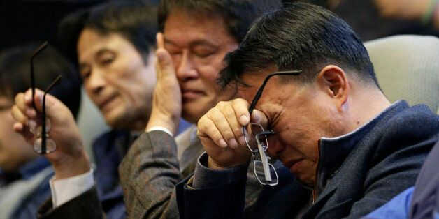 In this Friday, Nov. 7, 2014 photo, family members of passengers aboard the sunken ferry Sewol wipe their...