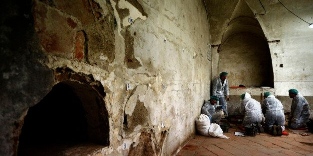 A team of archaeologists and anthropologists take notes after starting the excavation work after identifying...
